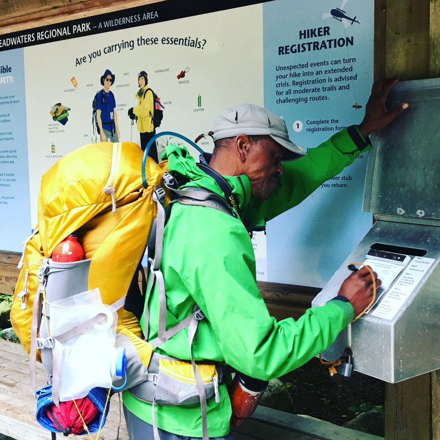 Man stands in front of an information board at the beginning of a hike. He is filling out a registration form with his trip plan.