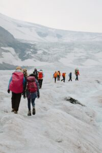 A group of people with large backpacks in single file doing an ice walk