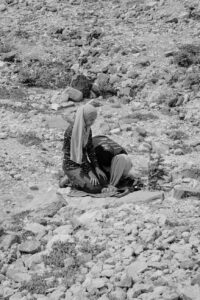 A black and white photo of two women in hijab in prayer in the outdoors