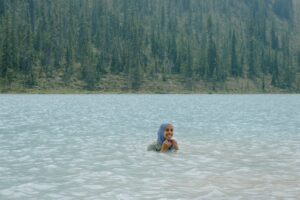 A woman in hijab smiles she stands in the lake, with a full forest of trees behind her.