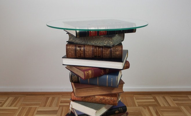 Stacking coffee table books to make a table is a clever solution for organizing clutter