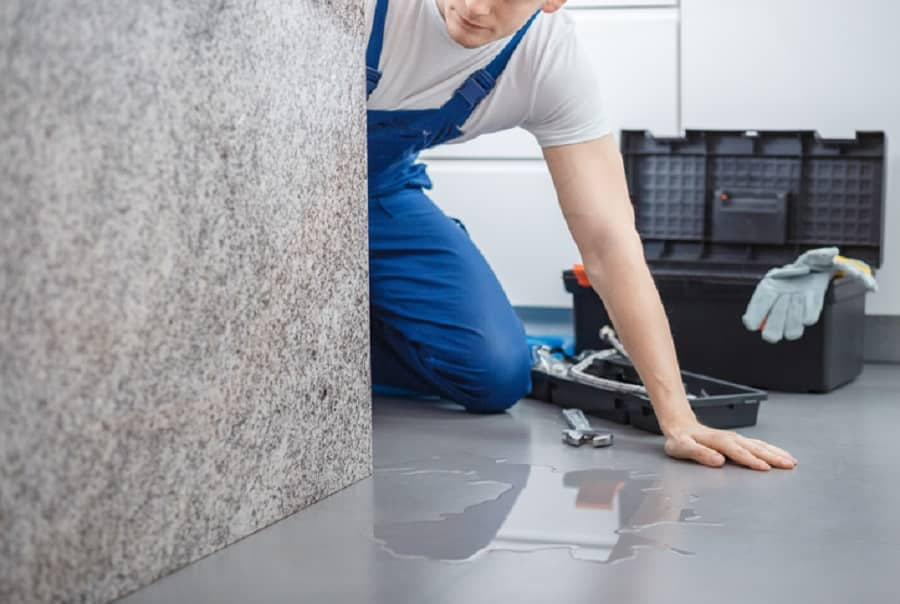 Plumber with toolbox looking at water on the floor from broken dishwasher