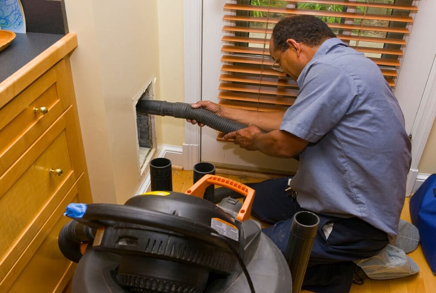 Worker-with-vacuum-during-duct-cleaning-in-home-1