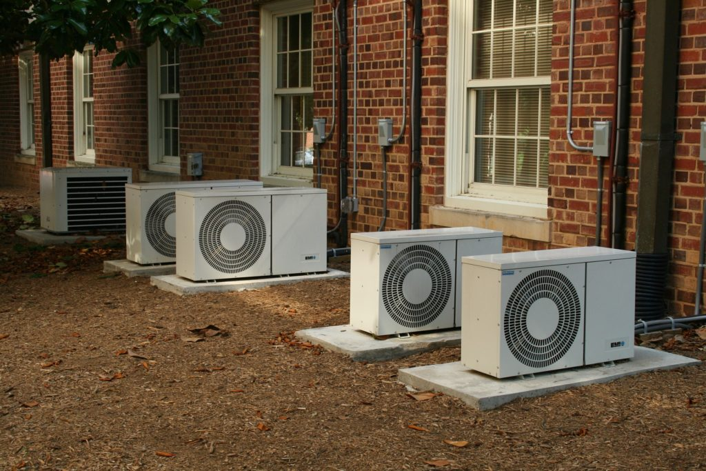 Air conditioners lined up outside a home