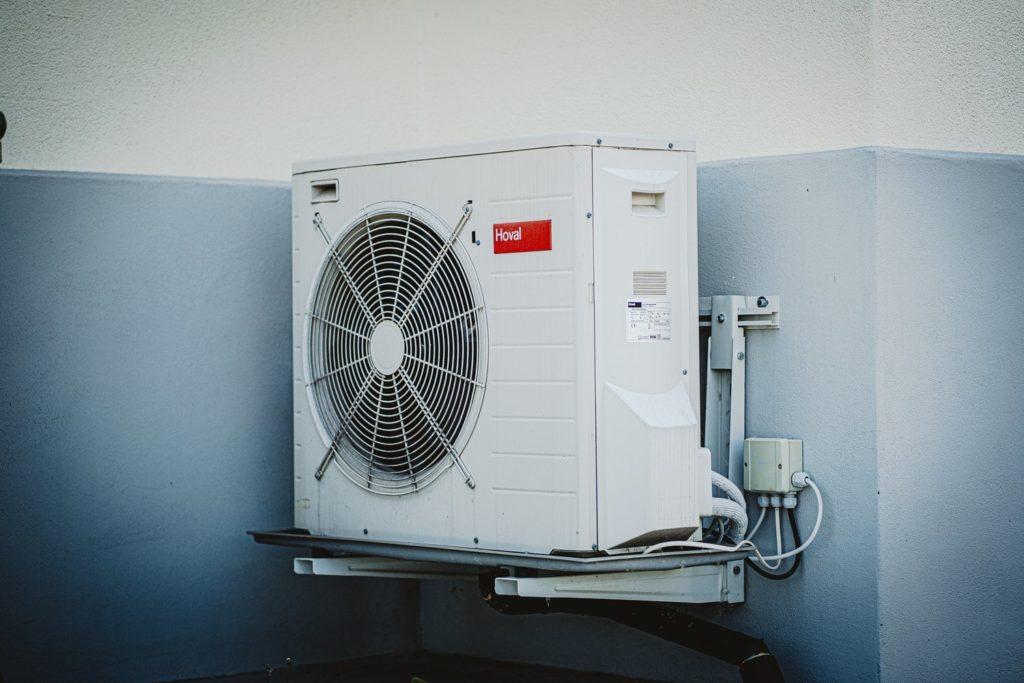 an air conditioner along a blue wall