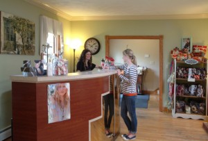 A woman talking to the receptionist before her appointment at the Coventina Day Spa's hair salon in Waterford, PA