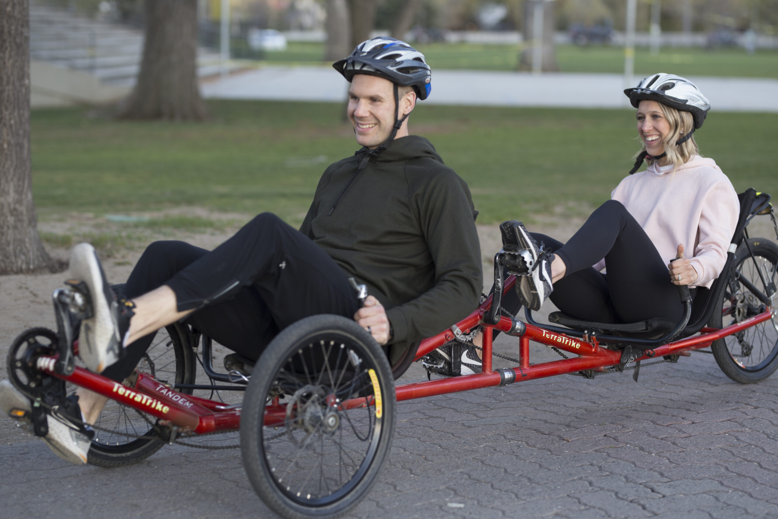 A man (in front) and a woman (behind) riding a red tandem recumbent cycle