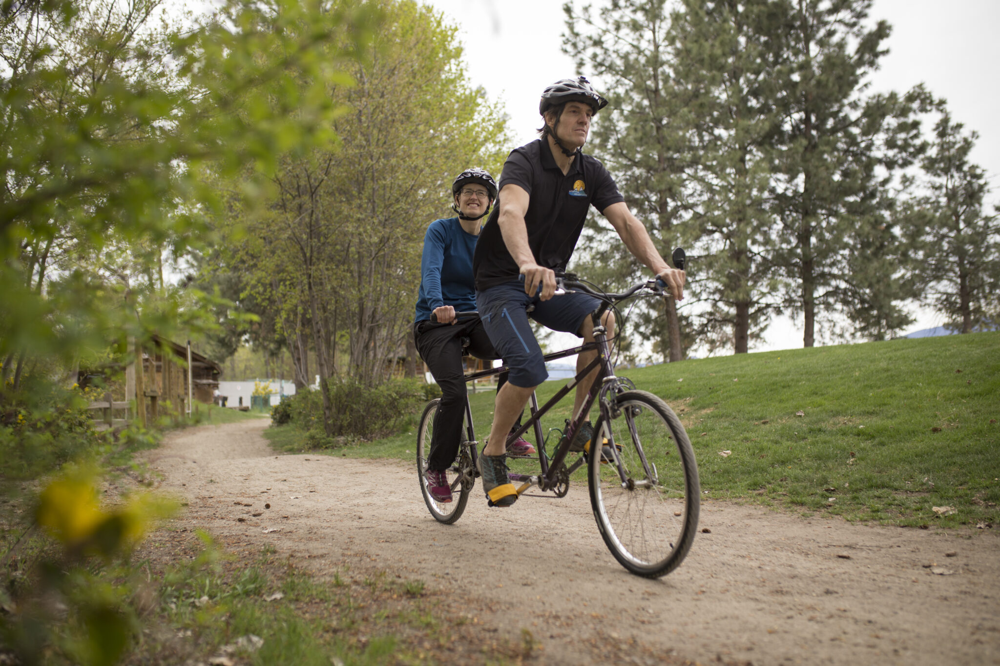 a man and a woman using a dark purple tandem upright cycle on a forest path.