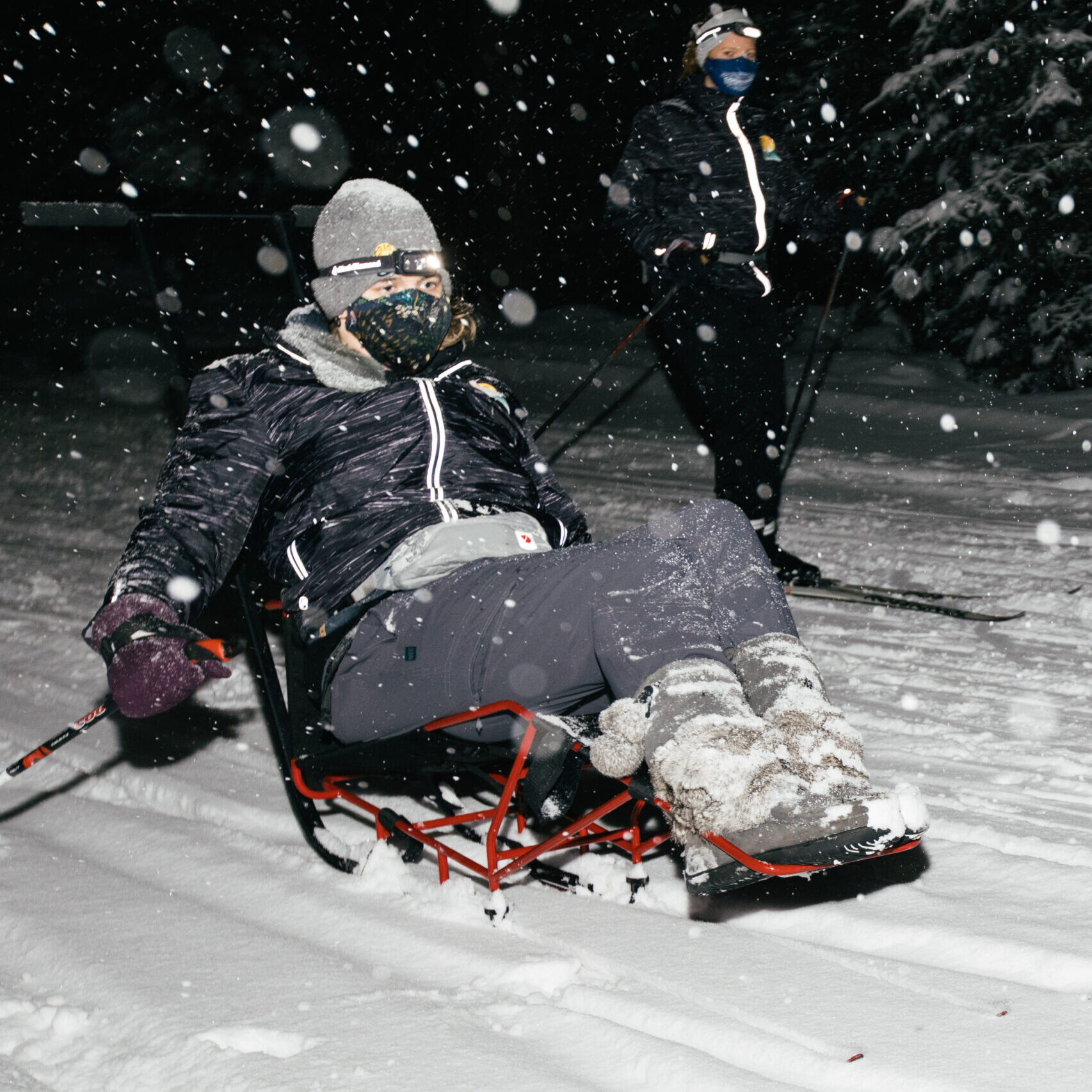 A woman using s nordic sit-ski at night during a snowstorm at night.