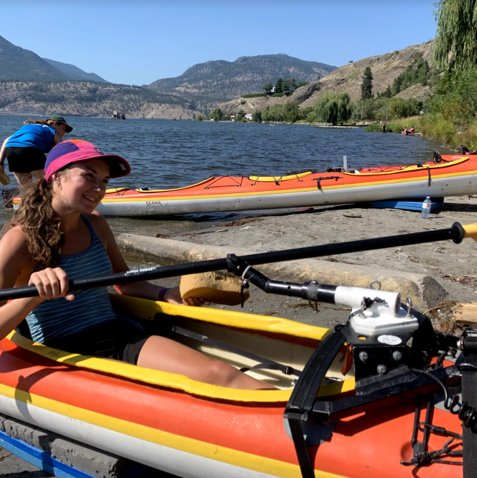A woman in a kayak on the shore, demonstrating the one-armed rigger.