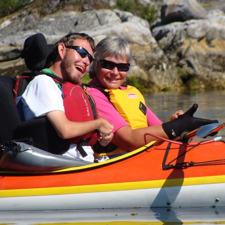 A man and a woman in separate kayaks. The man is being handed a black paddle. The man is seated in black supportive seating, similar to that of a wheelchair.