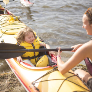 A woman handing a young girl in a kayak a paddle. The kayak is in the water.