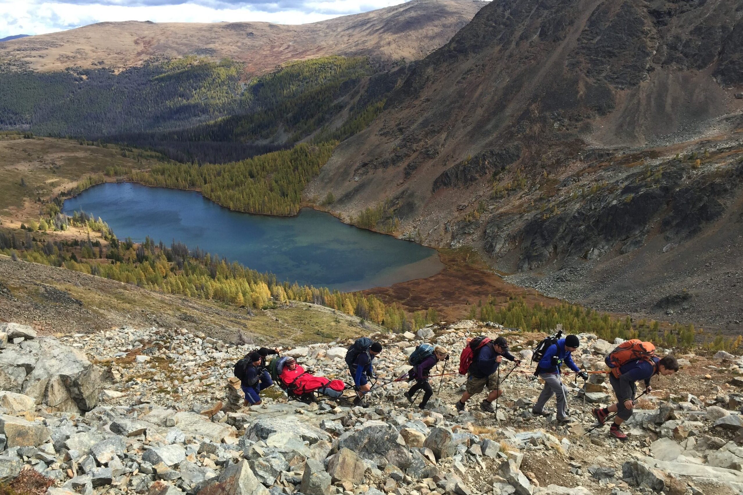 Seven hikers in rocky terrain. One is using a trailrider. There is a blue lake in the background.