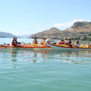 a group of kayakers in tandem kayaks in crystal blue waters