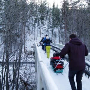 Volunteers pulling and pushing a pulk across a snow-covered bridge in the wintertime