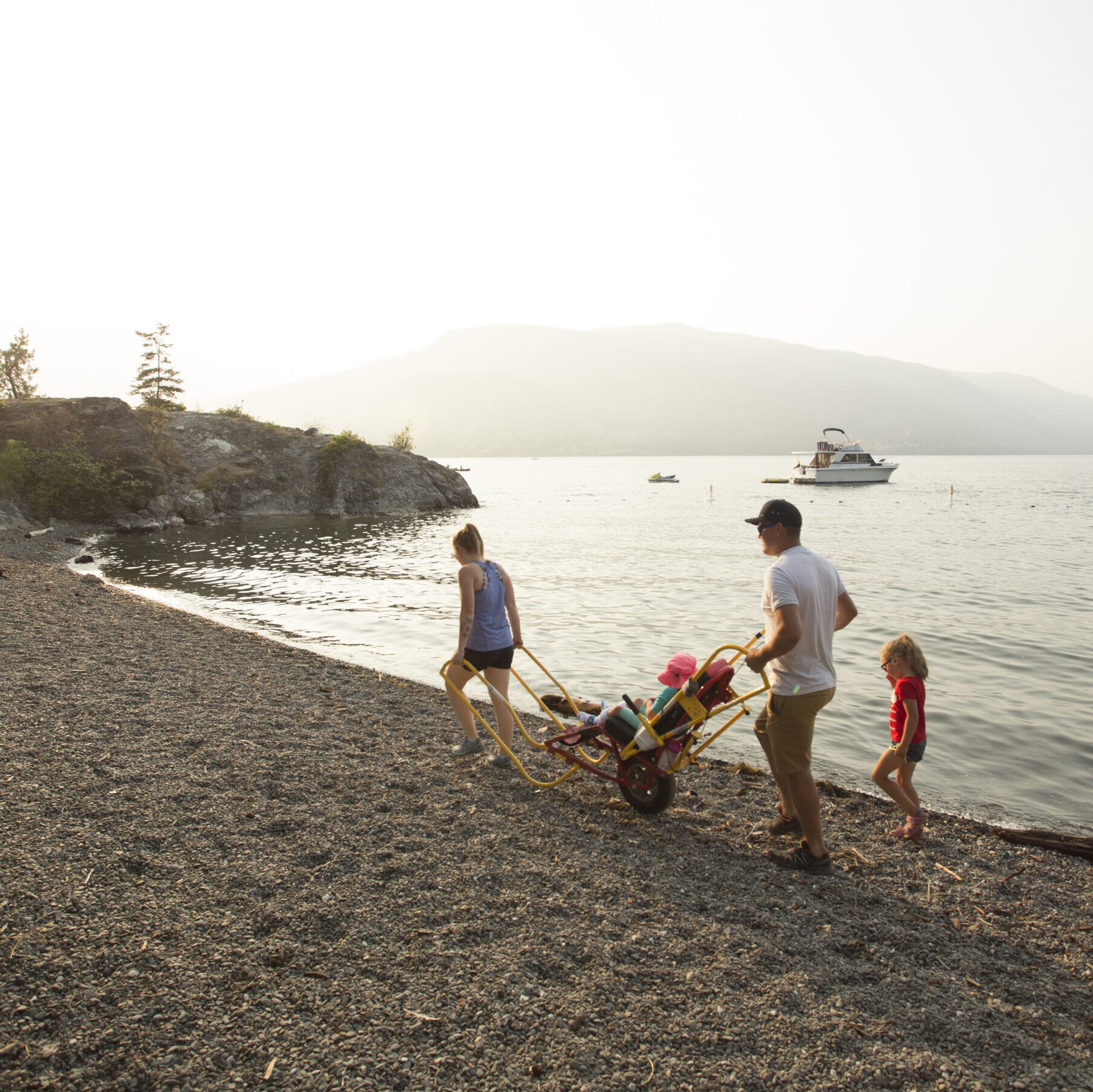 a family walking along the beach. one of the children is using a trail rider