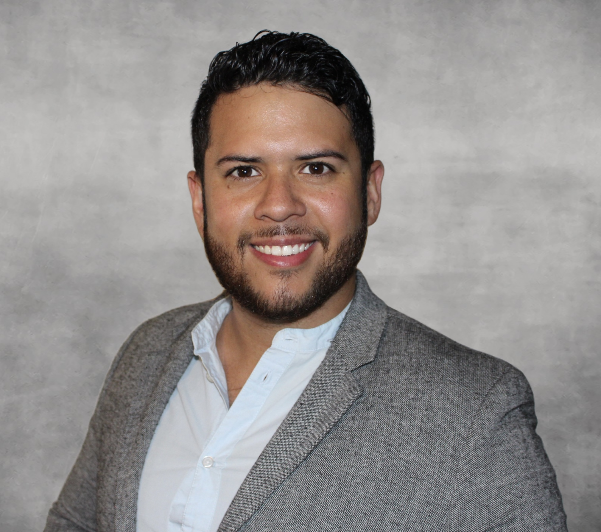 Dr. Jhonny Castro sporting a gray suitcoat and white button down, looking in to the camera in front of a gray background
