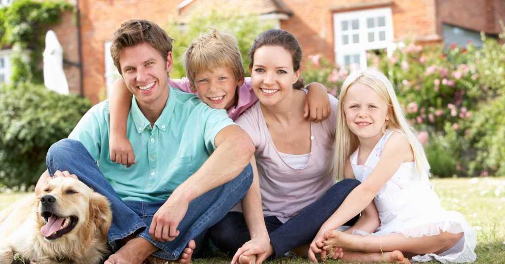 Smiling Family Outside Home
