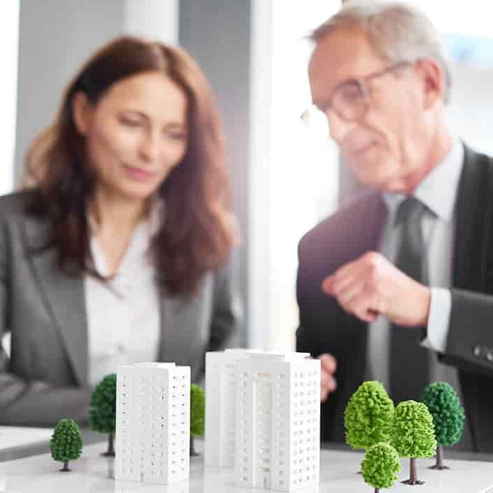 Man and woman sitting down in front of building model