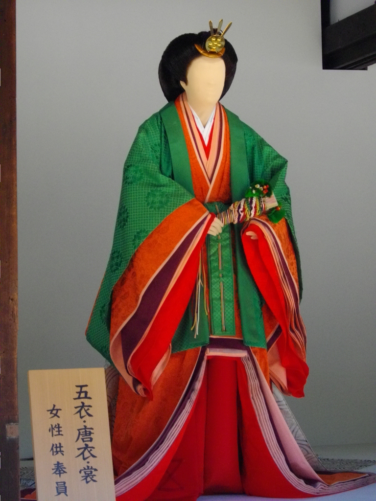 Mannequin dressed in itsutsuginu karaginu mo. There is a hiogi , folded, in the hands held at waist level.