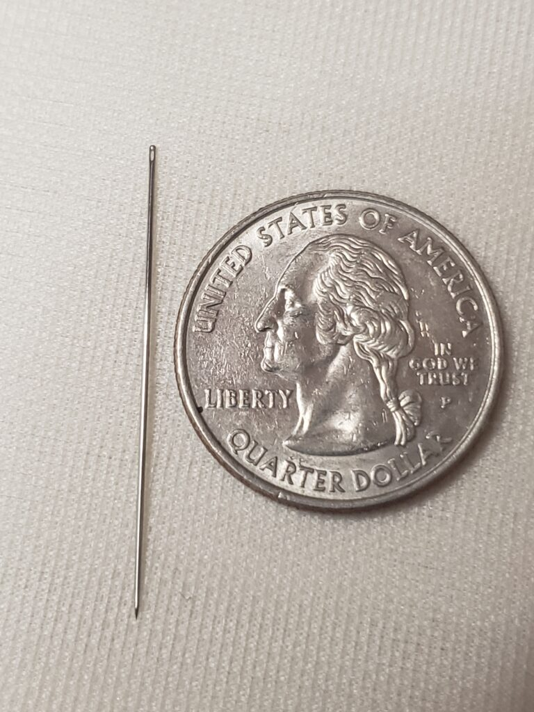 A needle to the left of a quarter.
