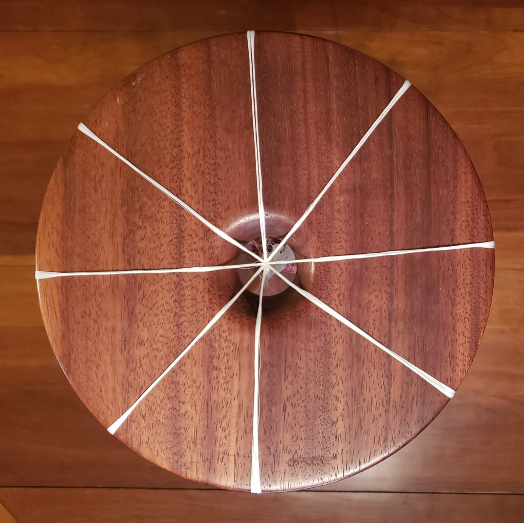 This is a top down view of a marudai set with 8 strands. we see a round wooden top divided evenly by 8 white strands that join in the center over a hole in the round top.