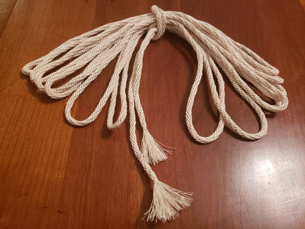 A looped bundle of white braided cord, kumihimo, with tasseled ends.