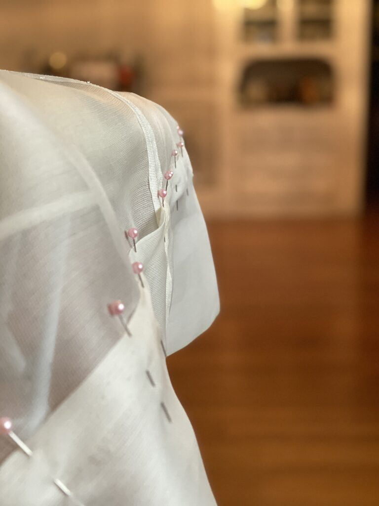 Fabric hangs over the edge of an ironing board. It has been folded back on itself and held in place by pink-headed straight pins.