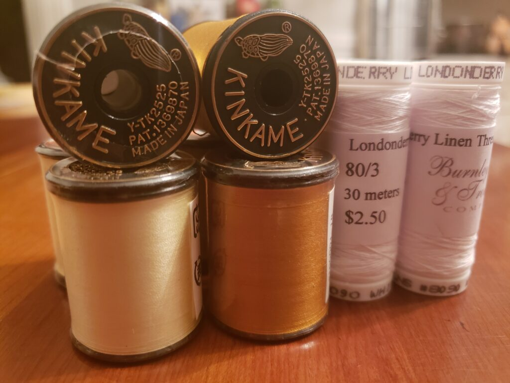 A collection of spools of thread. Left is Kinkame brand pale yellow, center is kinkame brand in gold. The kinkame spools have one spool standing on end and another laying on top with the end toward the camera. On the right are 2 spools of 80/3 Londonderry Linen thread in white from Burnley and Trowbridge .