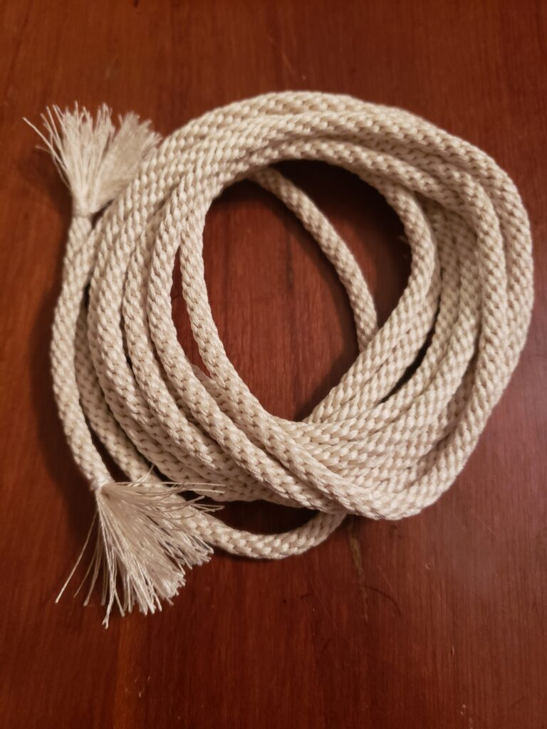 A coil of braided cord with tasseled ends.