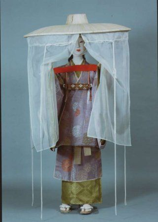 The Costume Museum mannequin of a lady wearing a travelling outfit and ichime gasa with mushi no tareginu or hemp veiled sedge hat. The mannequin stands with her hands outstretched parting the sheer curtains hanging down from the very wide brimmed straw hat.