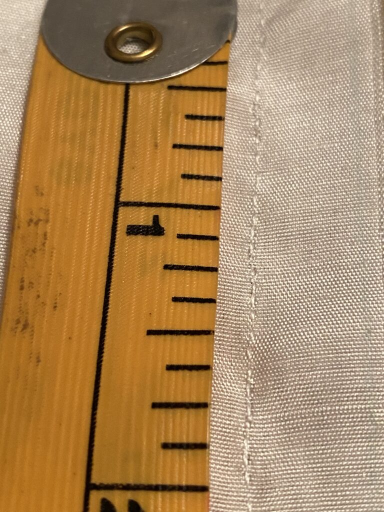 The first two inches of a yellow measuring tape next to a handsewn seam of approximately 20 stitches per inch.