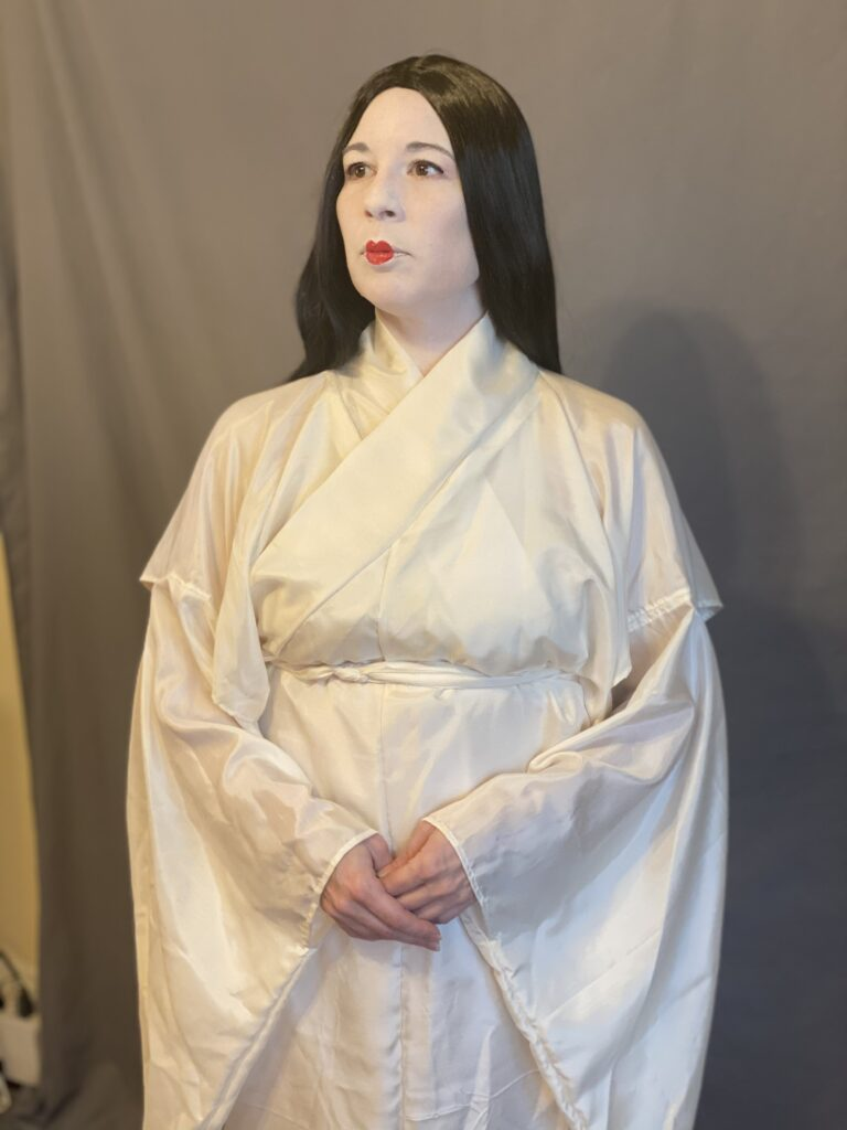 A woman with Heian make up (white face and small red lips) wearing a white silk kosode.