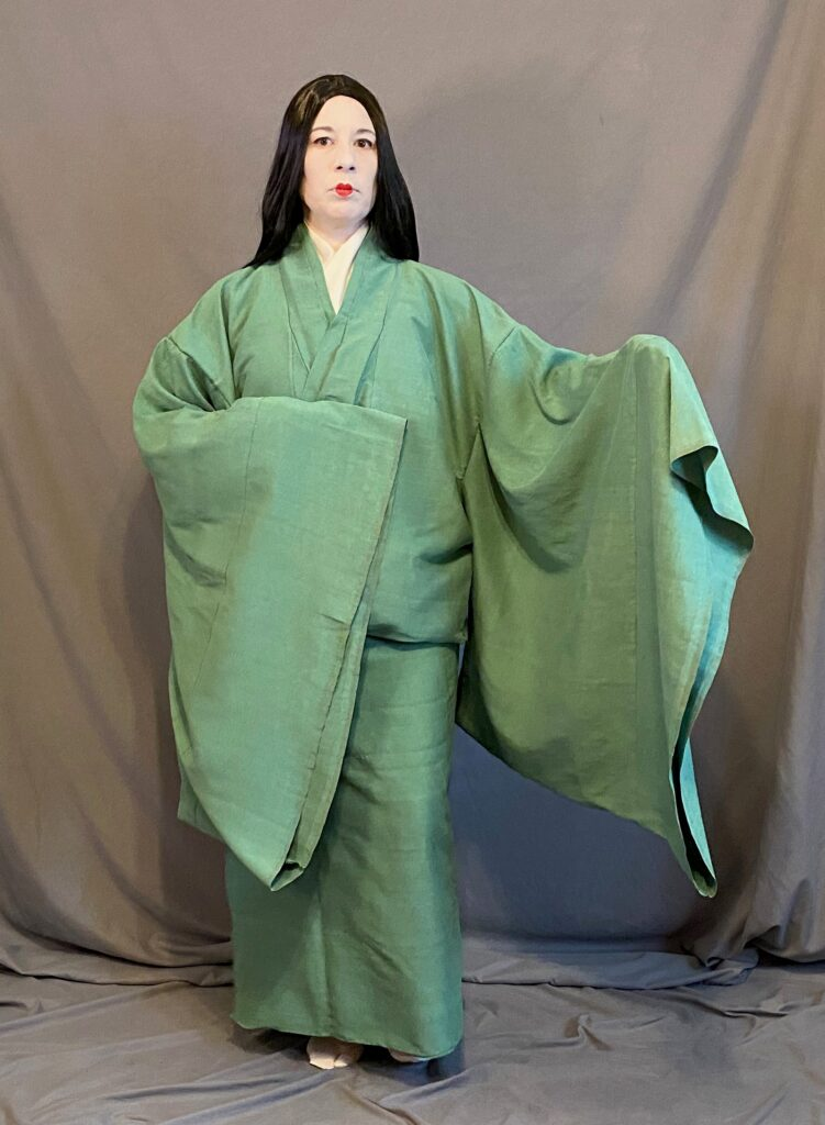 A woman in Heian make up (white face and small red lips) wearing a hitoe, belted up at the waist, with one arm outstretched to display the large sleeves.