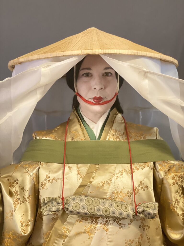 A woman wearing a Heian travelling outfit, the veil panels on the large hat spread wide to reveal her face and clothing.
