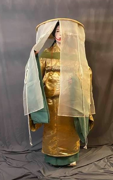 a woman in Heian make up (white face with small red lips) wearing a travelling outfit of several robes and a large, veiled hat with decorative cords