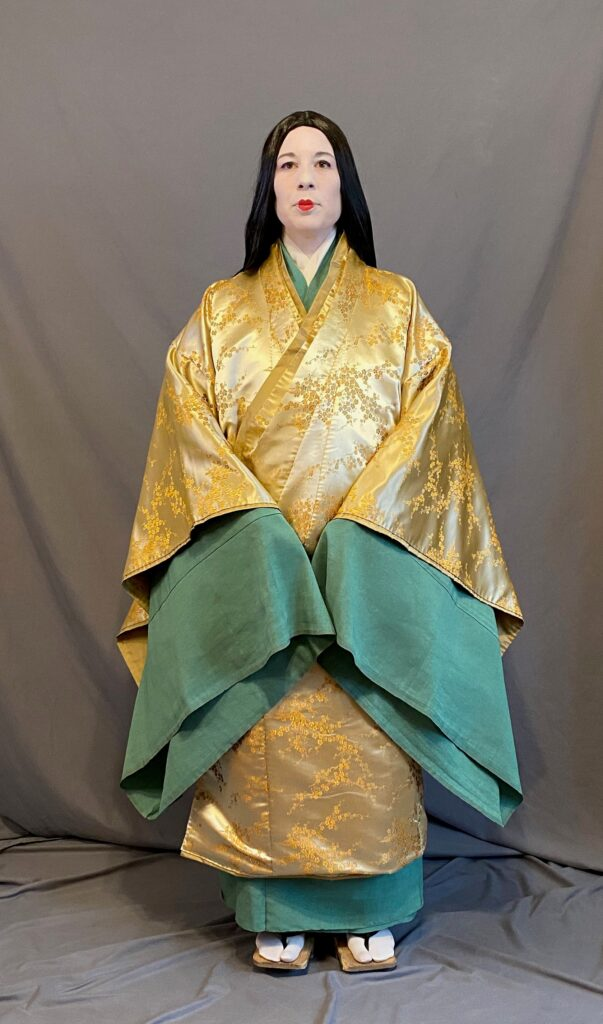 A woman in Heian make up (white face with small red lips) wearing a brocade uwagi over kosode and hitoe The longer green hitoe sleeves show vividly against the gold brocade of the uwagi
