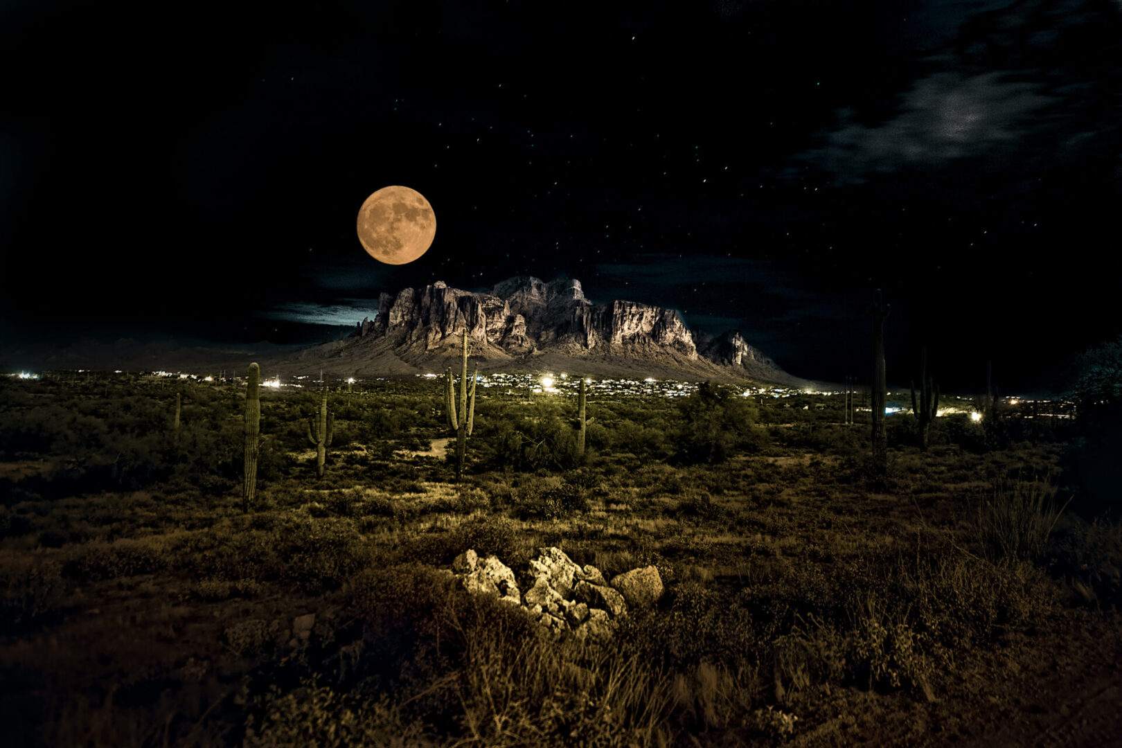 A harvest moon rises over the Superstition Mountains and the village of Apache Junction