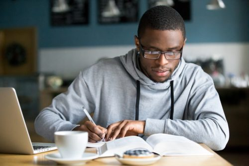 Young Adult writing on pad of paper on desk. Computer and coffee also on table