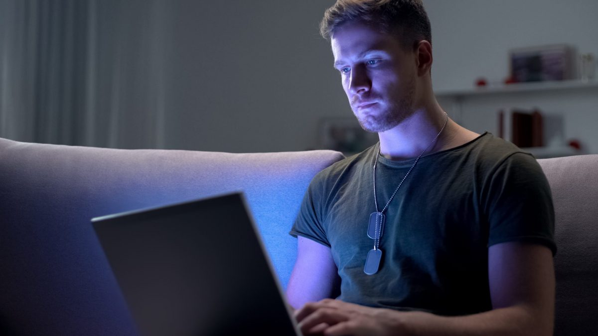 Young adult male with army dog tags working on laptop in dark room