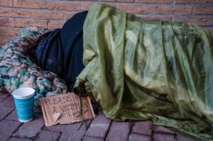 Homeless Female Veteran Sleeping Against Brick Building