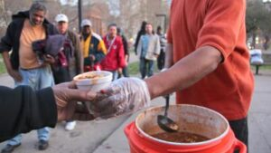 man serving food to homeless