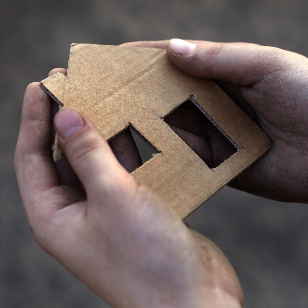 hand holding cardboard house