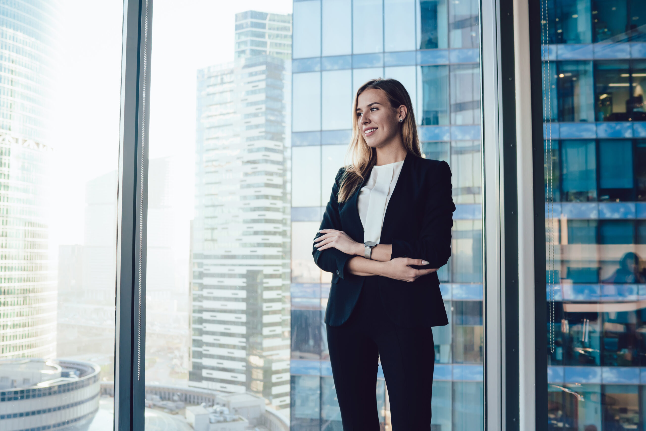 Smiling blonde woman in trendy suit posing in office interior near window with panoramic view on business center, cheerful prosperous female proud ceo in formal outfit standing with crossed hands