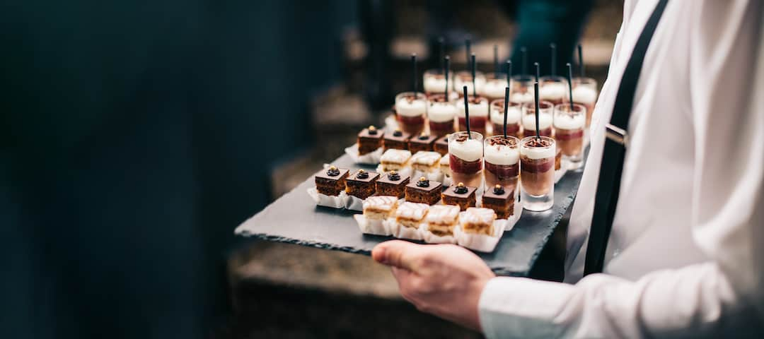 Waiter serving desserts on a tray to demonstrate reopening of restaurant after COVID-19 testing.