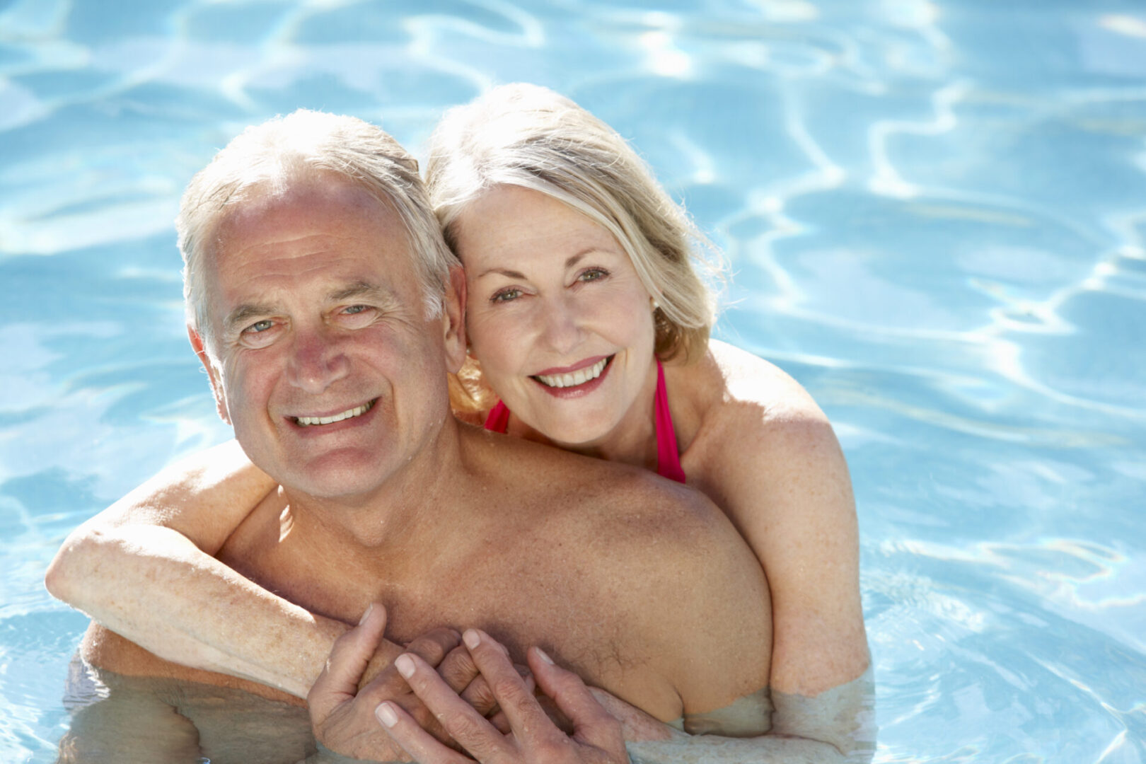 Senior,Couple,Relaxing,In,Swimming,Pool,Together