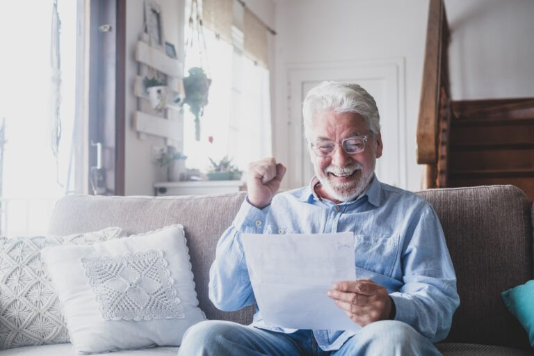 Excited elderly man celebrate health insurance deal closing looking and reading results.