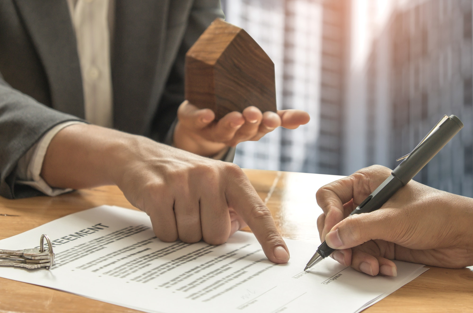 Home brokers and buyers signing a sale contract.
