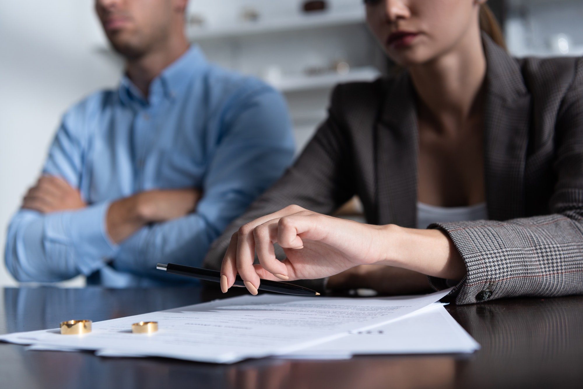 partial view of couple at table with divorce documents
