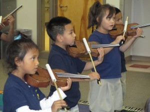 Swansea kindergarten students practice on their paper violins, preparing for their first concert and the presentation of their real violins